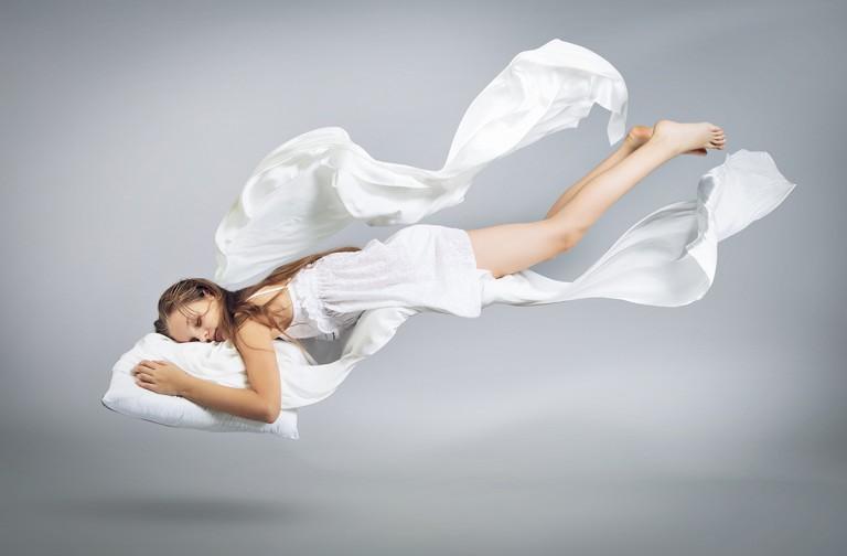Sleeping girl. Flight in a dream. White linen flies through the air. Light gray background